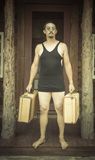 Gentleman Dressed in 1920's Era Swimsuit Holding Suitcases on Stock Image