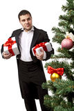 Gentleman with gift boxes. Gentleman standing  near a Christmas tree with gift boxes. Isolated over white background Stock Image