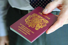 Gentleman handing over his British passport Royalty Free Stock Photo