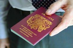 Gentleman handing over his British passport Royalty Free Stock Photo