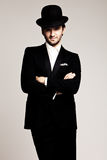 Gentleman with hat. Elegant young man in black tuxedo and derby,studio shot Royalty Free Stock Photos