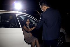 Gentleman Helping Date Out of a Car. Asian male gentleman assisting his black female date out of a car.  The image depicts interracial dating and manners or a Stock Image