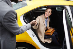 Gentleman Helping Young Woman Leave Taxi. Portrait of African American gentleman helping young smiling Asian women get out of taxi holding her by hand royalty free stock image