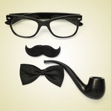 Gentleman or hipster guy. A pair of glasses, a mustache, a bowtie and a smoking pipe on a beige background depicting a gentleman or a hipster guy, with a retro Royalty Free Stock Images