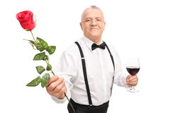Gentleman holding a glass of wine and a rose Royalty Free Stock Image