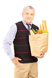 Gentleman holding a paper bag full of food Stock Image