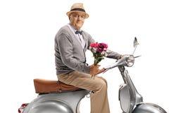 Gentleman på en sparkcykel som rymmer en bukett av blommor arkivbild