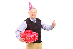 A gentleman with party hat holding a gift and giving a thumb up Stock Image