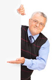 Gentleman posing behind a blank panel and gesturing Royalty Free Stock Photography