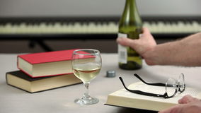Gentleman reading a book while drinking a glass of wine. Gentleman seated at his table reading a book while drinking a glass of wine and a piano in the stock video