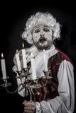 Gentleman rococo era wig, chandelier with candles. Gentleman rococo era wig, man dressed in vintage Royalty Free Stock Photo
