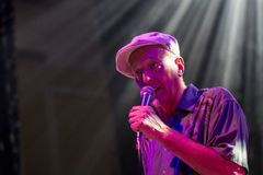 A gentleman singing with a microphone in a spotlight Royalty Free Stock Photography