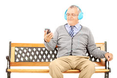 Gentleman sitting on a bench and listening music from his phone Royalty Free Stock Photos