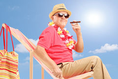 Gentleman smoking a cigar and enjoying on a chair on a sunny day Stock Image