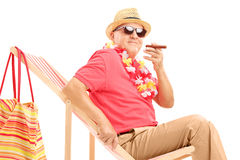 Gentleman smoking a cigar and enjoying on a sun lounger Stock Photography