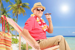 Gentleman smoking a cigar and enjoying on a sun lounger Stock Image