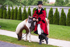 Gentleman with top hat and his pony. A gentleman with a beard in a riding suit posing for a photo leaning against a horse Royalty Free Stock Photo