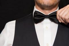 Gentleman in Waistcoat Straightens Bowtie. Stock Images