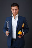 Gentleman wearing a tuxedo holding champagne bottle. Gentleman wearing a tuxedo holding a champagne bottle. A waiter, servant or bartender presenting beer or Royalty Free Stock Photos