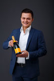 Gentleman wearing a tuxedo holding champagne bottle. Gentleman wearing a tuxedo holding a champagne bottle. A waiter, servant or bartender presenting or Royalty Free Stock Image