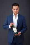 Gentleman wearing tuxedo holding a whiskey bottle. stock photos