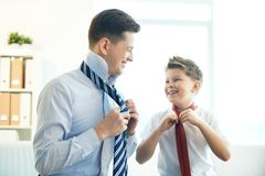 Gentlemen. Photo of happy boy and his father tying neckties Royalty Free Stock Photography