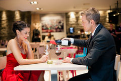 Gentlemen pouring wine his girlfriend Royalty Free Stock Photography