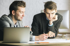 Gentlemen using computer and doing paperwork Royalty Free Stock Photography