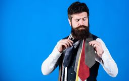 Gentlemens guide. How to choose right tie. Classic style. How to match necktie with shirt and suit. Man bearded hipster. Hold few neckties on blue background stock images
