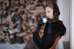 Gentlewoman que senta-se com o tampão do chá fora no inverno Foto de Stock Royalty Free