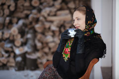Gentlewoman sitting with cap of tea outdoors at winter Royalty Free Stock Photo