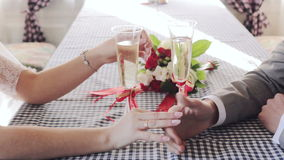 Gently connected hands of a newly-married couple. With wedding rings on a finger on a background of a glasses of champagne stock video