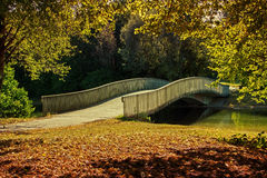 Gently curved bridge in the park Stock Images