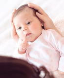Gently mother hands holding baby . Plump and beautiful newborn Royalty Free Stock Photos