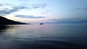 Dawn Light Highlighting Gentle Sea Water Ripples, Gulf of Corinth Bay, Greece. Gently rippled sea water highlighted by pink and blue early morning dawn light. A stock video footage