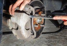 Removing caliper while replacing car brakes stock photo