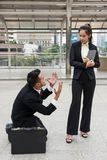 Genuflexión del hombre de negocios de la tensión al bos de la mujer foto de archivo