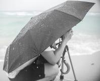 Genuflexión en lluvia por el mar foto de archivo