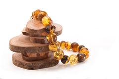Genuine amber. Amber necklaces and ring sections of tree trunk on white background Stock Image