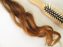 Genuine auburn hair strand and a hairbrush Royalty Free Stock Photography