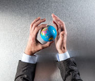 Genuine businessman hands holding planet for concept of international ecology. Genuine businessman hands holding the planet for concept of international ecology Stock Images