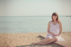Genuine cute pregnant lady woman in white airy dress sitting sand beach wooden palette bridge holding tummy abdomen. Attractive be. Autiful young girl enjoying Stock Photos