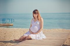 Genuine cute pregnant lady woman in white airy dress sitting sand beach wooden palette bridge holding tummy abdomen. Attractive be. Autiful young girl enjoying Stock Photo