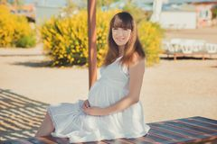 Genuine cute pregnant lady woman in white airy dress walking sand beach wooden palette bridge holding tummy abdomen. Attractive be. Autiful young girl enjoying Stock Photo