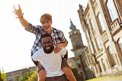 Genuine goofy guy having fun with his friend. Like kids. Strong enthusiastic charming men giving his fellow student a ride while goofing around at the university stock photo