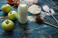 Genuine ingredients for the cake - apple, milk, flour, eggs and cacao on blue rustic table. Genuine ingredients for the cake - apple, milk, flour, eggs and cacao Royalty Free Stock Image