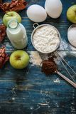 Genuine ingredients for the cake - apple, milk, flour, eggs and cacao on blue rustic table. Genuine ingredients for the cake - apple, milk, flour, eggs and cacao Royalty Free Stock Images