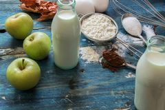 Genuine ingredients for the cake - apple, milk, flour, eggs and cacao on blue rustic table. Genuine ingredients for the cake - apple, milk, flour, eggs and cacao Stock Photos