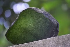 Genuine jade is a natural lump. That has not yet been cut. Dark green, rare and stock photos