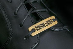 Genuine Leather. Extreme close-up of a black men's shoe with 'Genuine Leather' tag Royalty Free Stock Photography